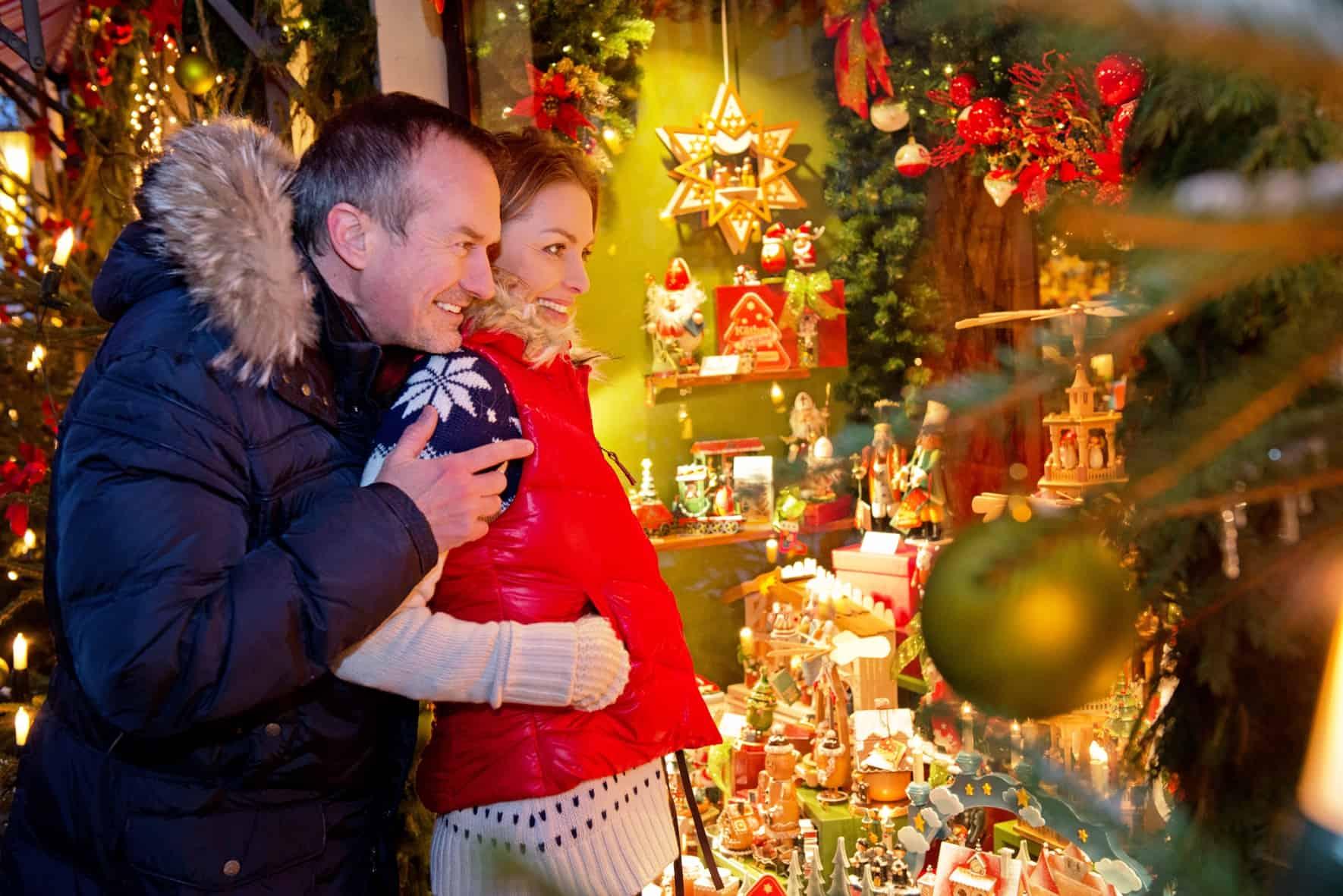 Junges Paar schaut sich Geschenke auf dem Weihnachtsmarkt an