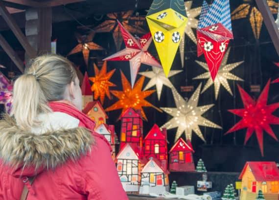 Junges Mädchen bewundert Deko Sterne auf dem Weihnachtsmarkt