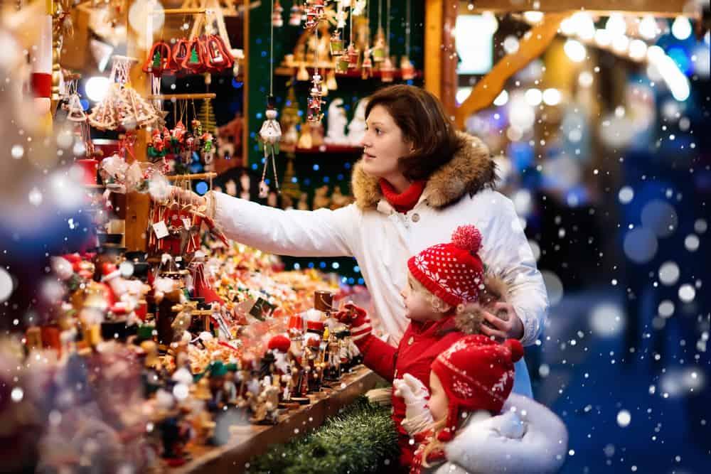 Mutter und Kind stehen vor einer Weihnachtsmarkt Verkaufsbude