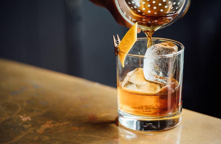 Cocktail wird in Glas mit Eiswürfel gefüllt