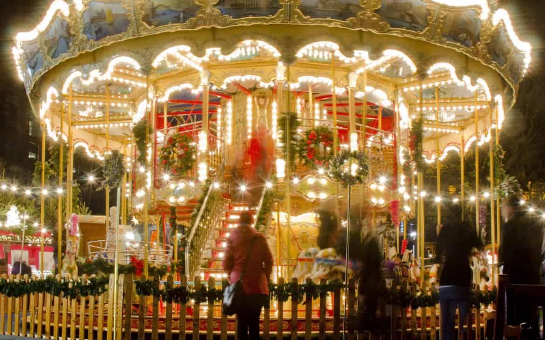 Frau steht vor beleuchtetem Karussel auf Weihnachtsmarkt in Edinburgh