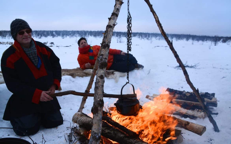 Mann erheizt Suppe über Lagerfeuer in verschneiter Landschaft