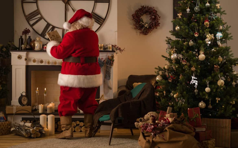 Nikolaus verteilt Geschenke vor Kamin