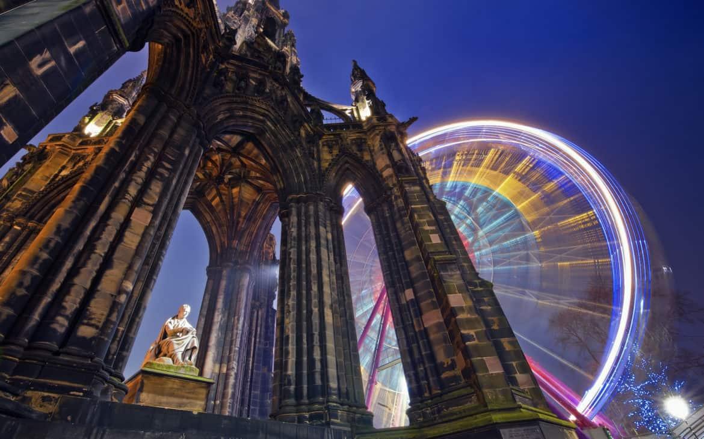Beleuchtetes Riesenrad vor Denkmal in Edinburgh