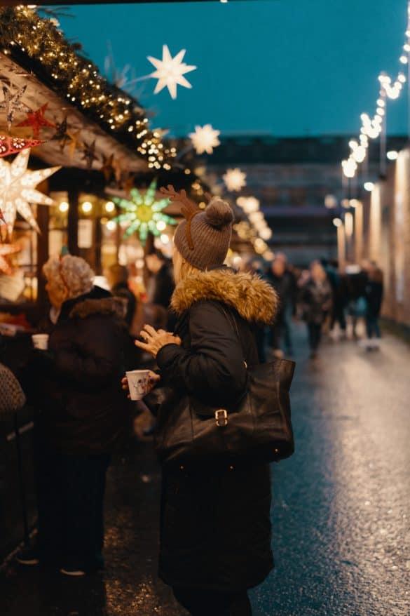Frau spaziert über Weihnachtsmarkt in Edinburgh