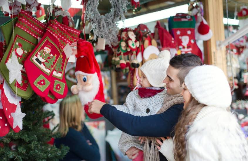 Familie schaut sich Nikolausfiguran auf dem Weihnachtsmarkt an