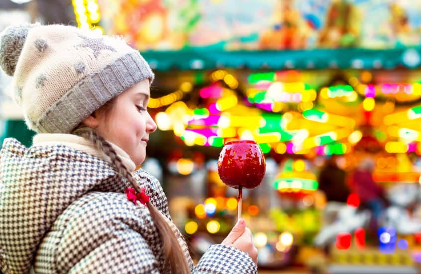 Mädchen freut sich über kandierten Apfel