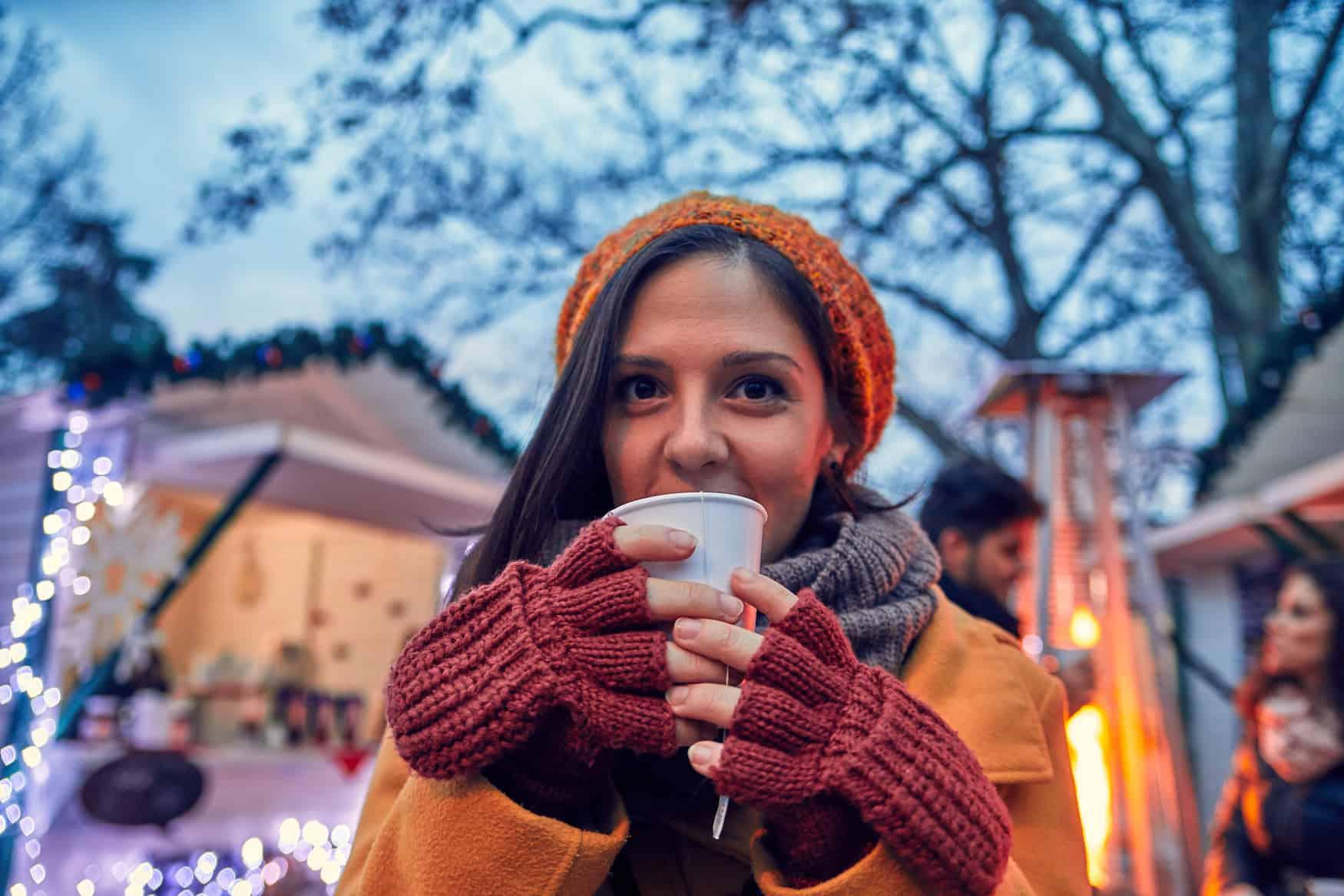 Dame trinkt Glühwein auf dem Weihnachtsmarkt