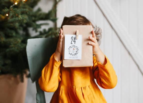 Kleines Mädchen hält sich Geschenk ihres Adventskalenders vors Gesicht