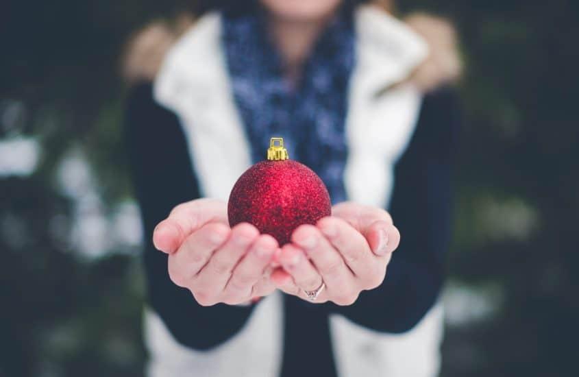 Frau hält rote Weihnachtskugel in Händen
