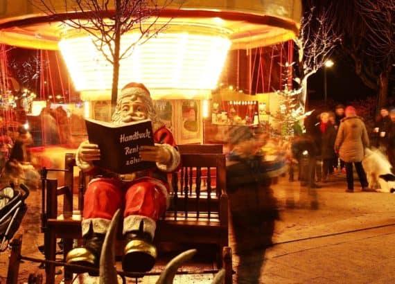 Nikolaus sitzt auf der Bank am Weihnachtsmarkt