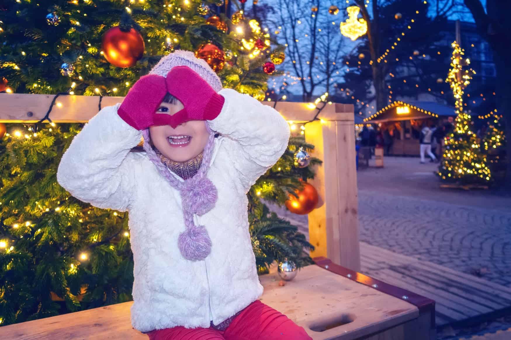 Kind fröhlich auf dem Weihnachtsmarkt