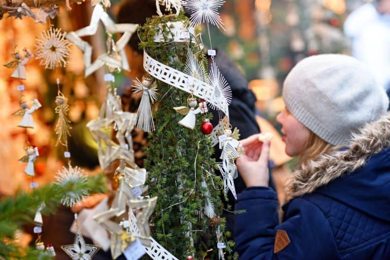 Junge Frau bestaunt Auslage Weihnachtsmarktbude