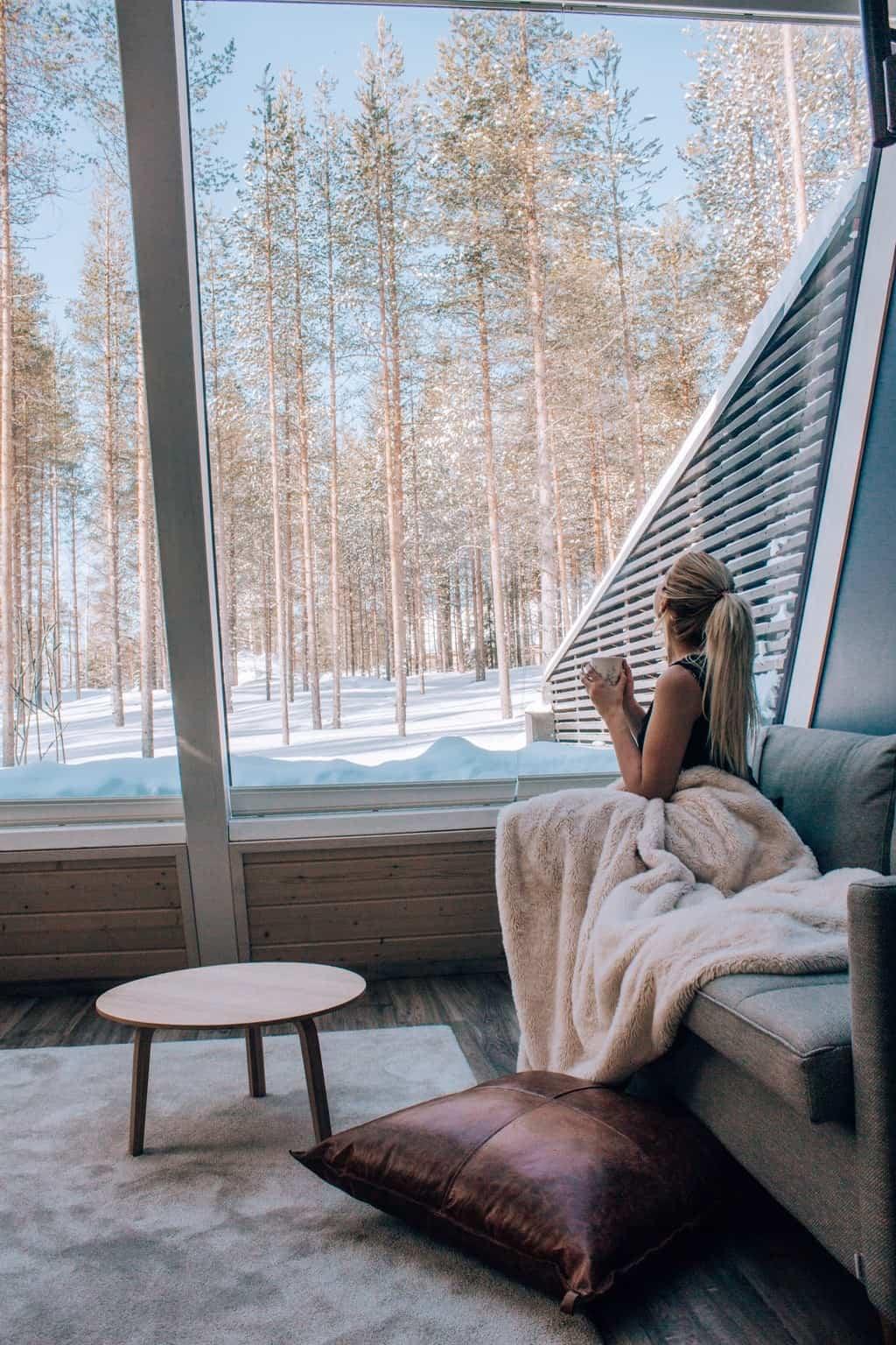 Frau blickt aus Glashotel auf verschneites Lappland