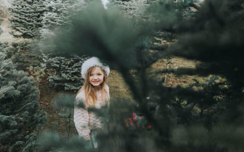 Kleines Mädchen mit Weihnachtsmütze steht zwischen Tannenbäumen