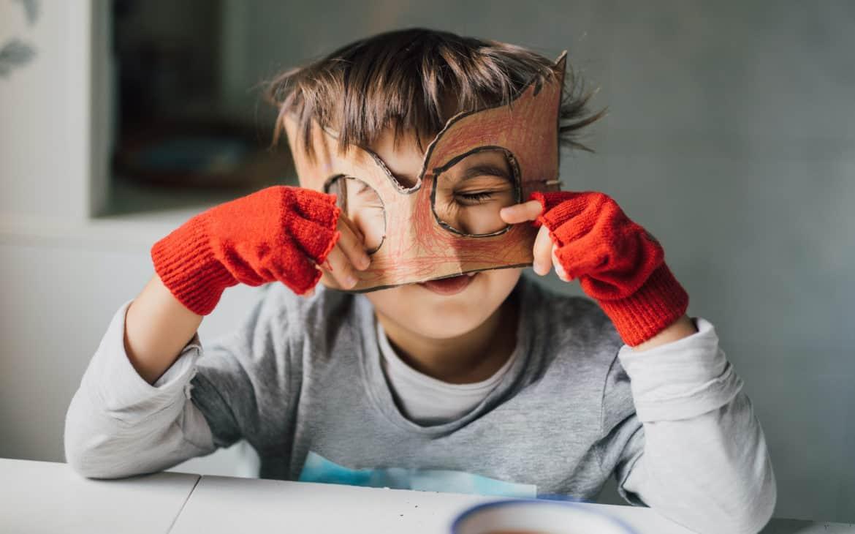 Kind mit selbstgebastelter Superhelden-Maske