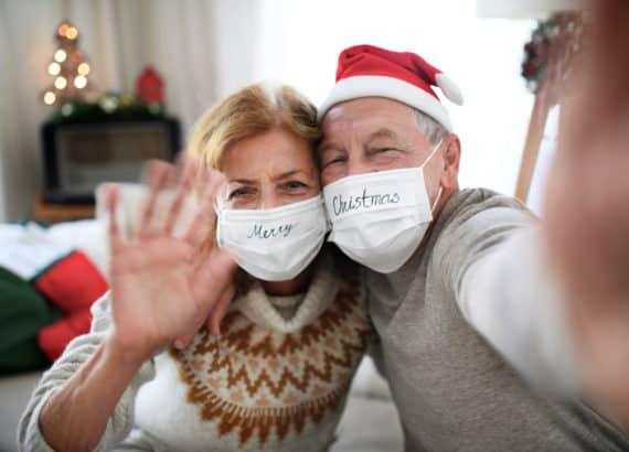 Älteres Pärchen hat Maske und Weihnachtsmützen an und winkt in die Kamera während Weihnachten im Corona Jahr