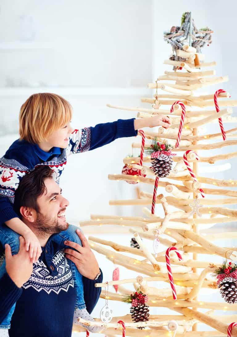 Vater und Sohn schmücken alternativen Weihnachtsbaum aus Holz