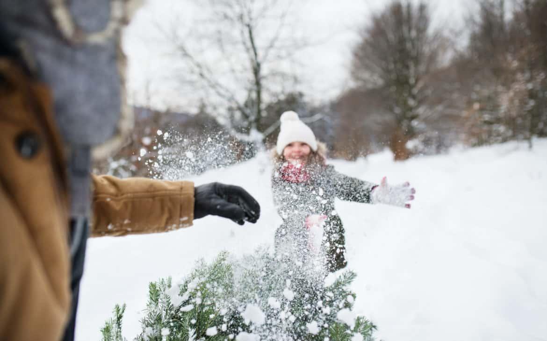 Mädchen und Vater beim Weihnachtsbaumweitwerfen in Wald