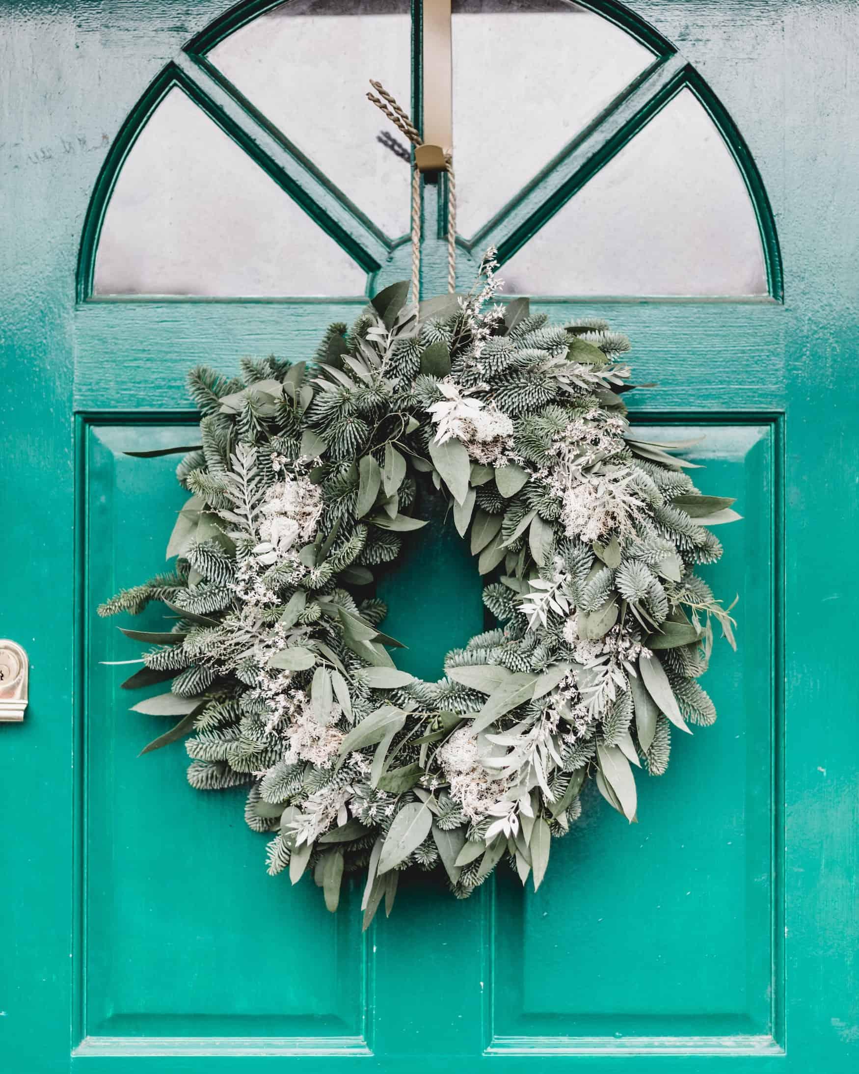 Weihnachtlicher Kranz an türkisfarbener Haustür