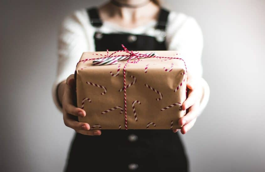 Frau hält Weihnachtsgeschenk in die Kamera